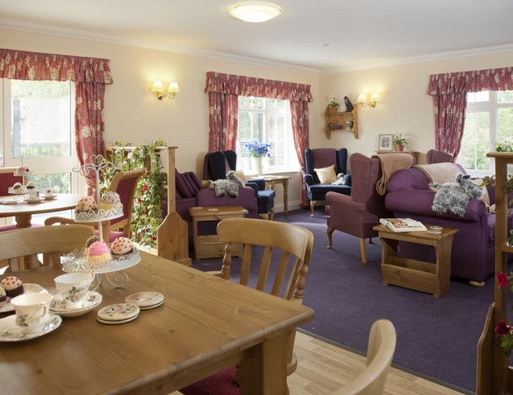 Large room with purple furniture on one side of the room and a dining tables with cakes on it on the other side