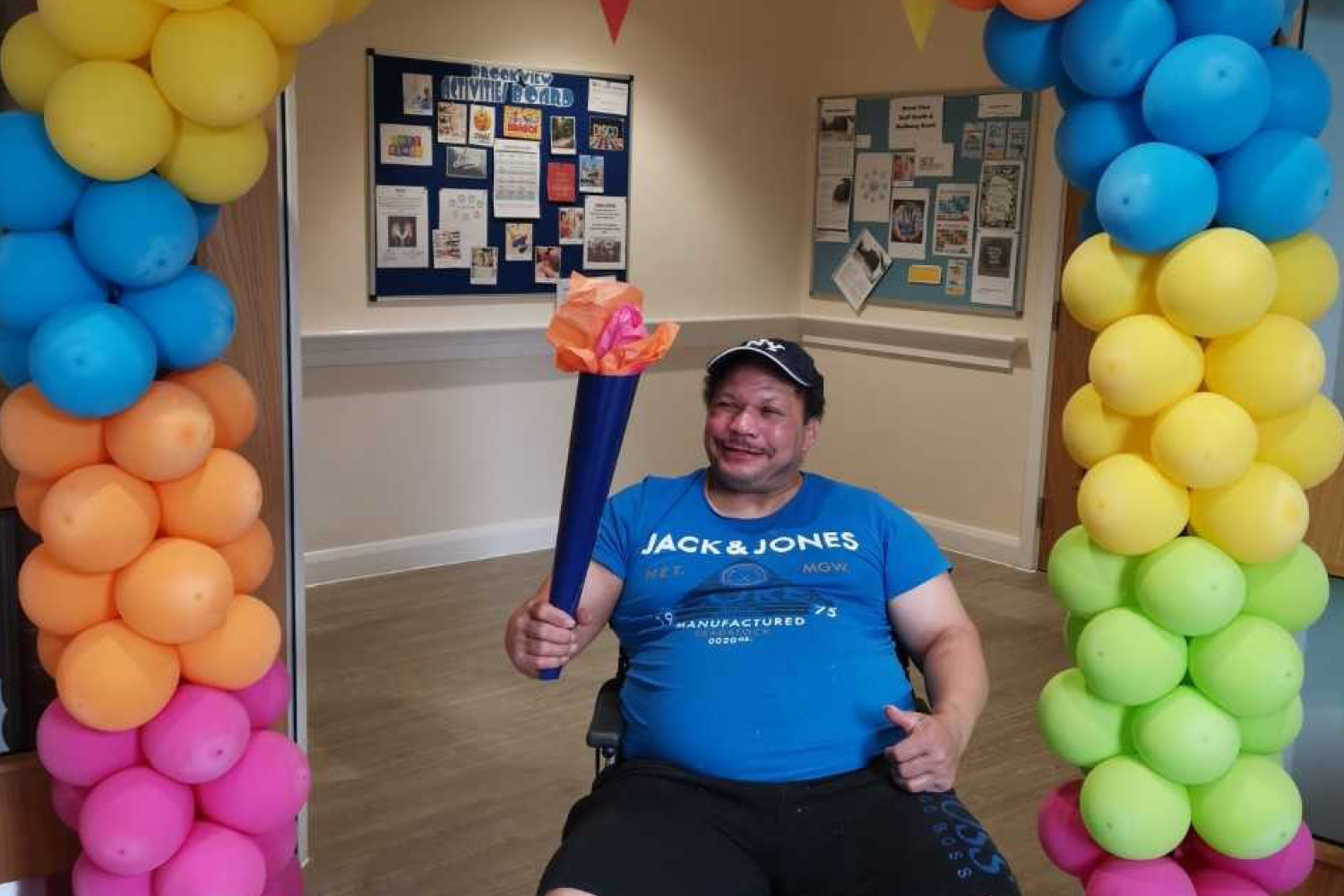 A male holding an Olympic torch under a balloon arch