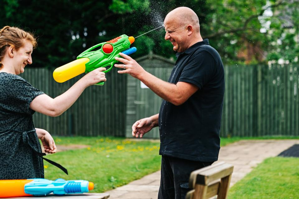 Young woman squirting water gun at male carer