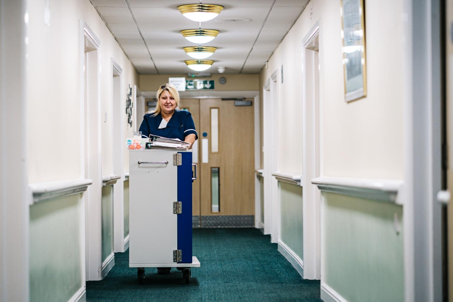 Picture of female nurse in care home with medication trolley