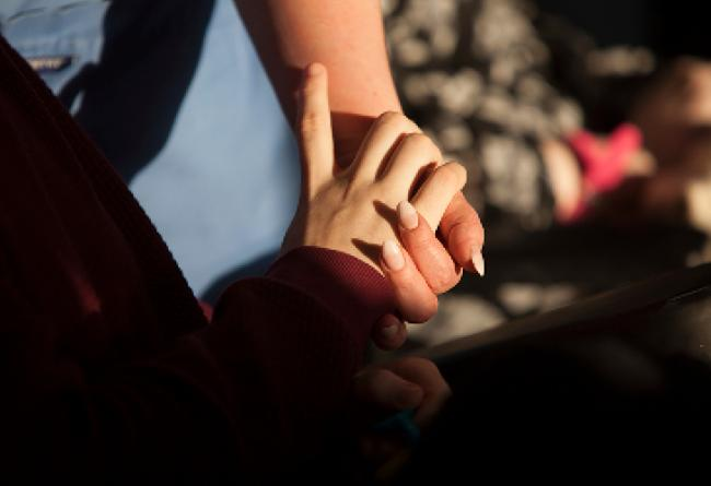 Service user and carer holding hands