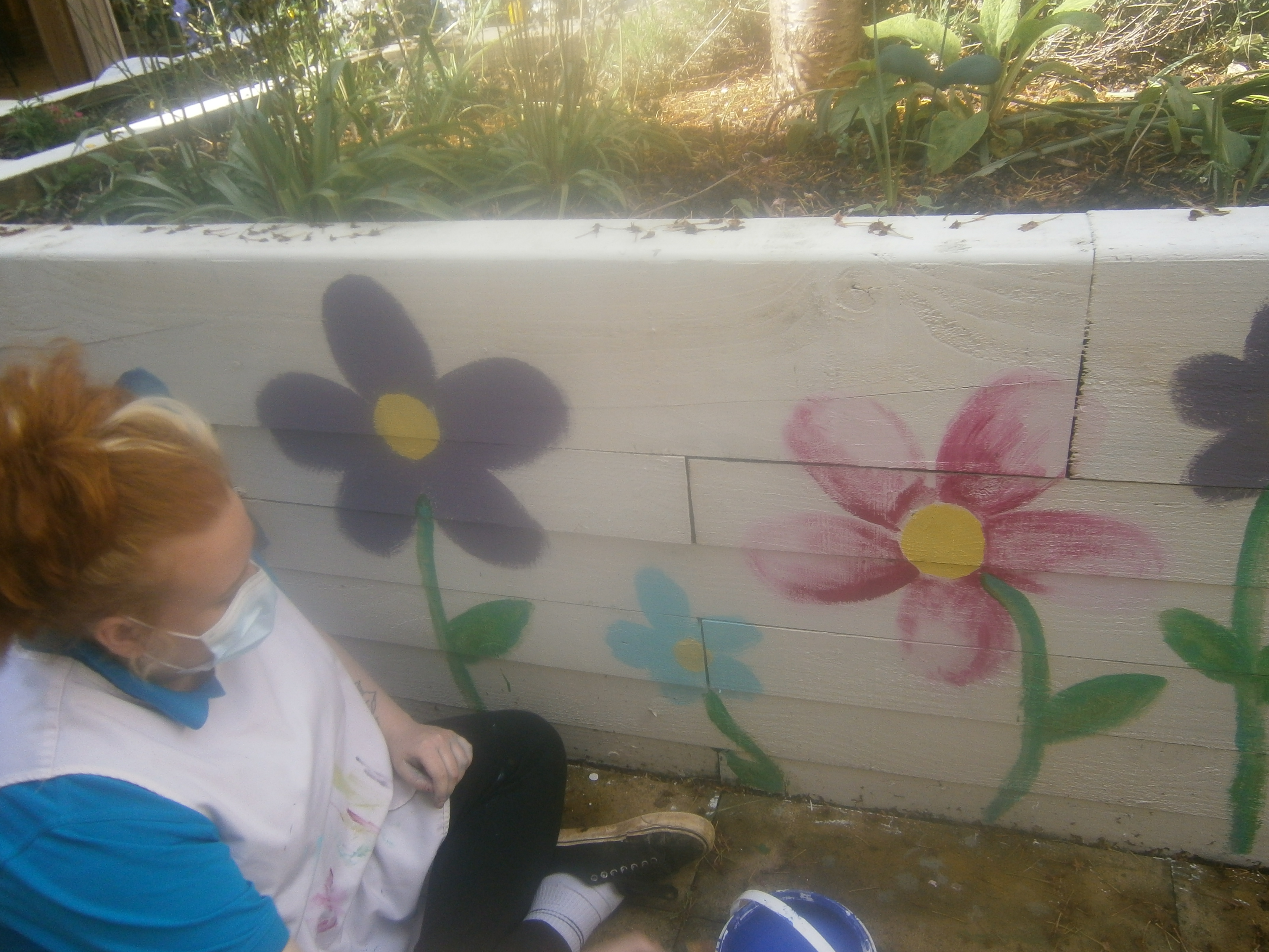 Leah painting flowers in the courtyard