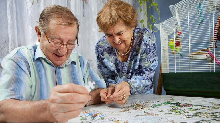 two older people doing a jigsaw