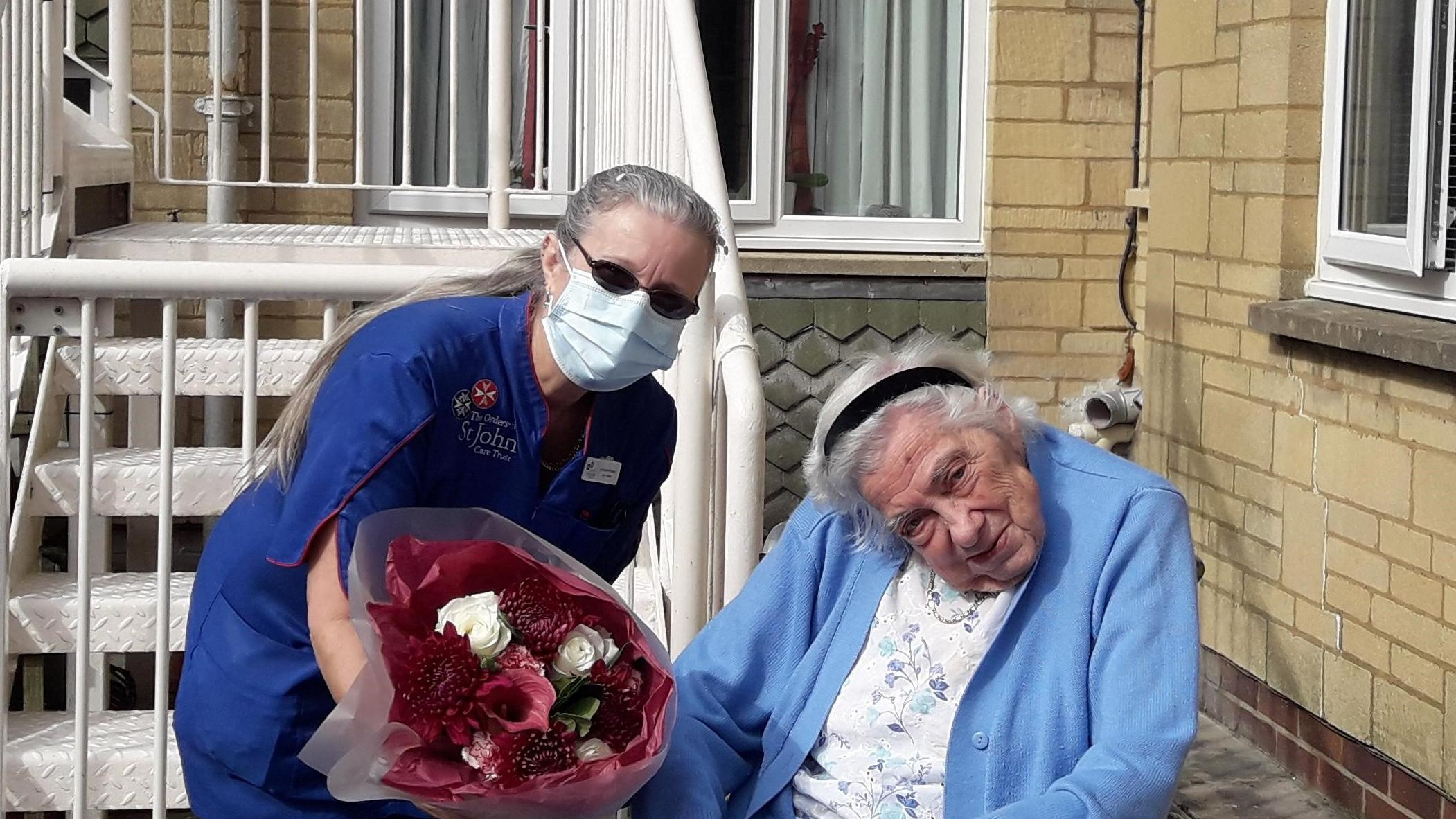 Lorraine presented with flowers by resident Margaret